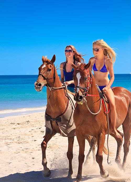 Girls horseback riding on beach in Punta Cana