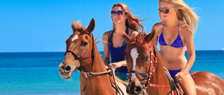 Escorts riding horses on beach at Senses Private Club