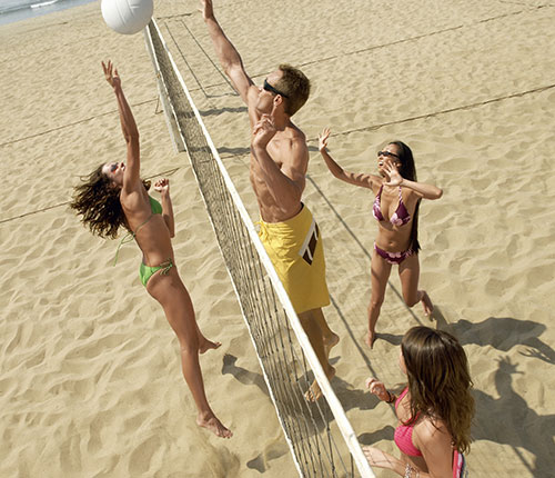 Swingers playing volleyball on beach