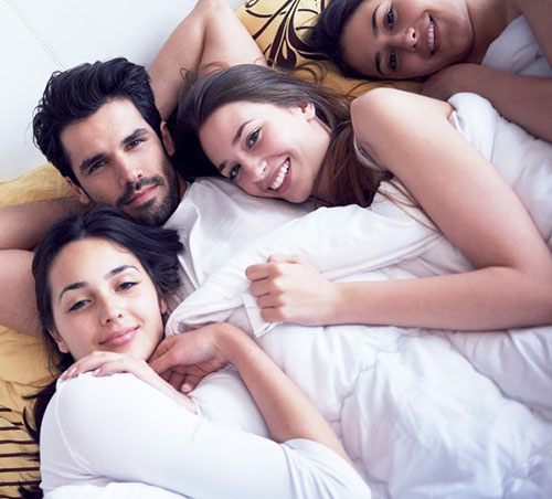 Group of swingers in bed
